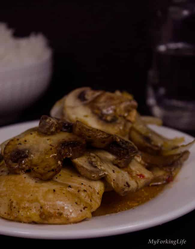 italian baked chicken and mushrooms on a plate with dark background