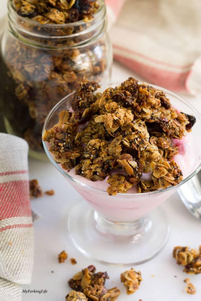 breakfast granola on top of yogurt in glass cup