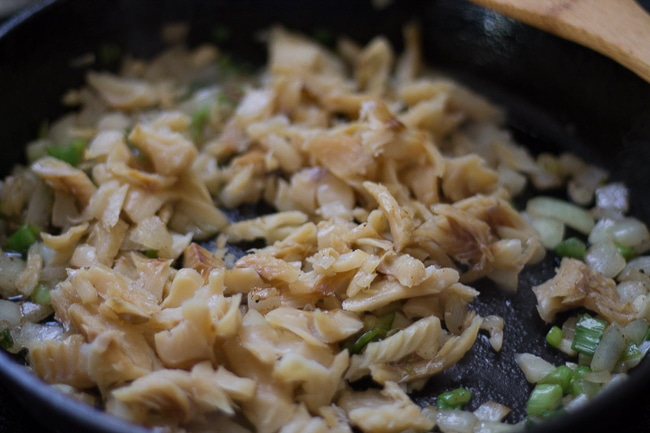 saltfish added to skillet with ingredients