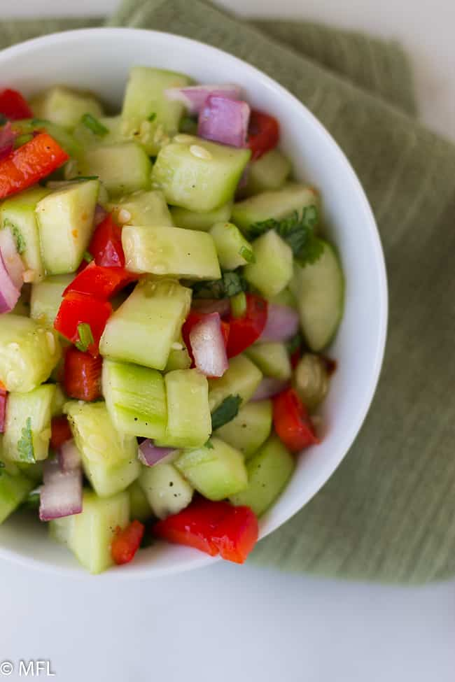 sweet chili thai cucumber salad and red peppers in white bowl