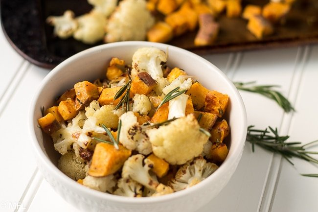 cooked cauliflower, sweet potato, and rosemary in white bowl with baking sheet in background