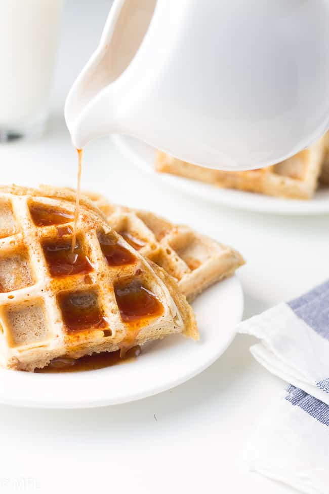 syrup being poured on waffle on white plate