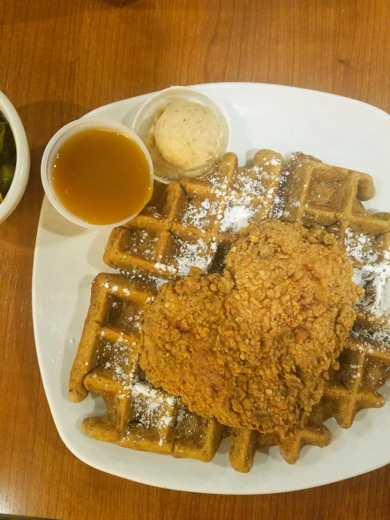 dame's chicken and waffles on white plate with sauce and butter on side