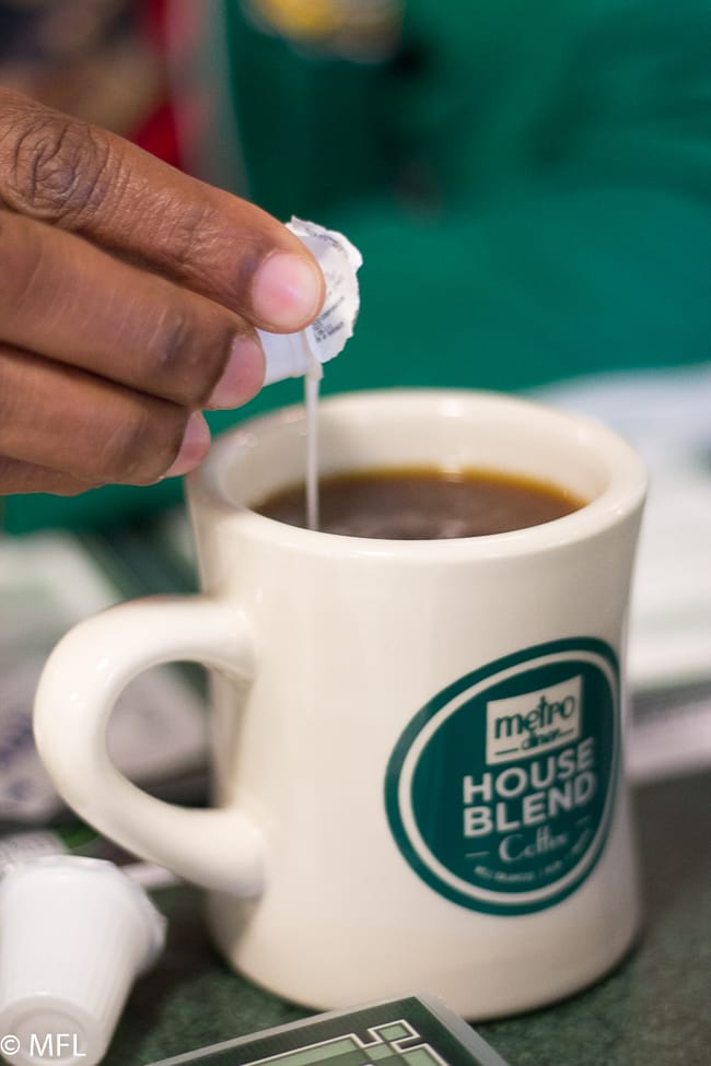 hand pouring creamer packet into coffee