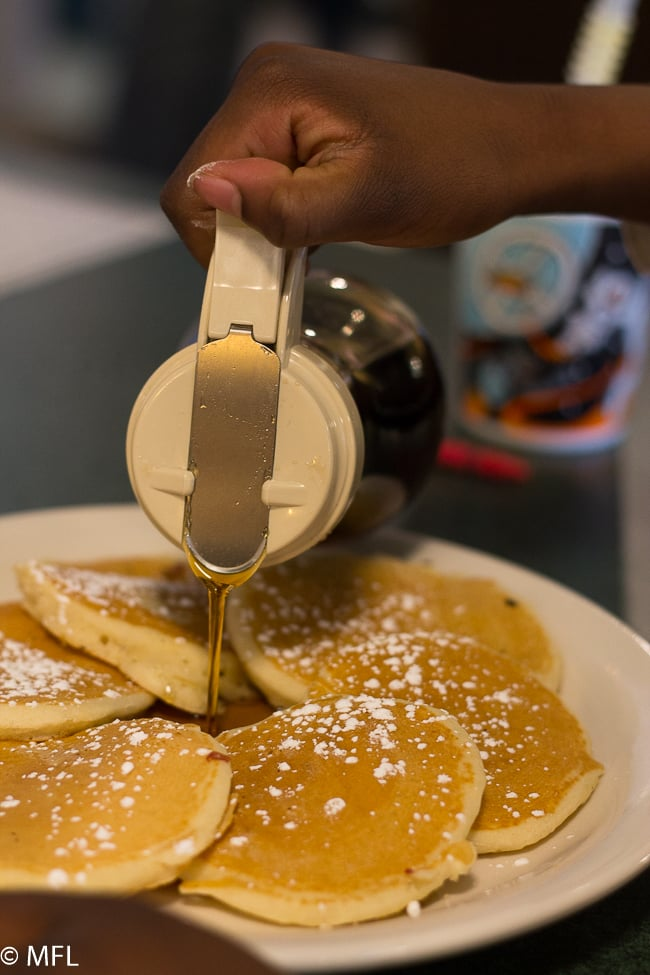 hand pouring syrup over pancakes