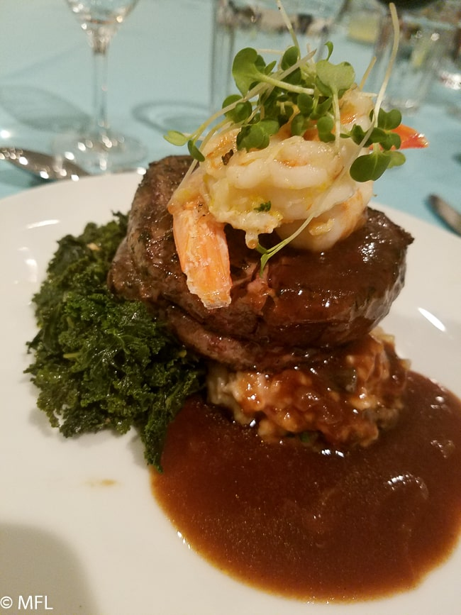 filet mignon with shrimp on top over kale and risotto