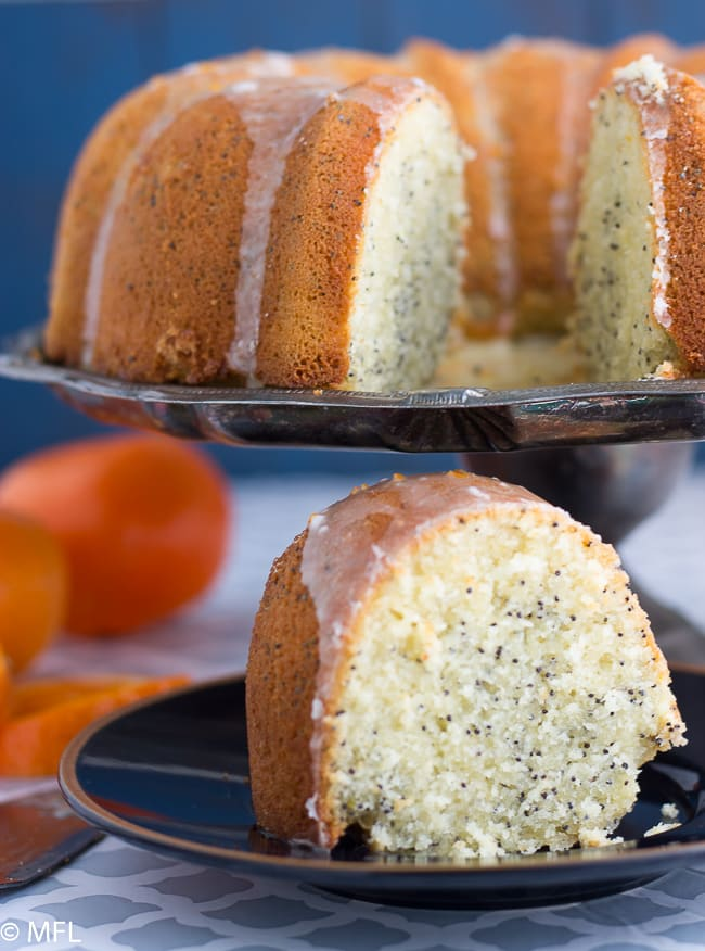 orange poppyseed bundt cake on cake pan with cake slice at bottom