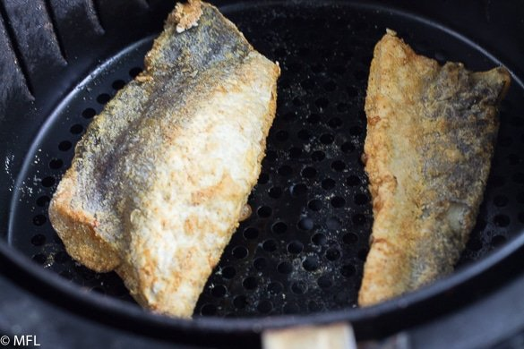 fish filets in air fryer basket after cooking