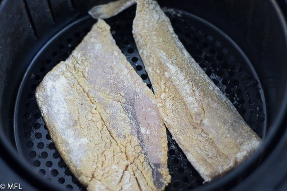 fish filets in air fryer basket before cooking