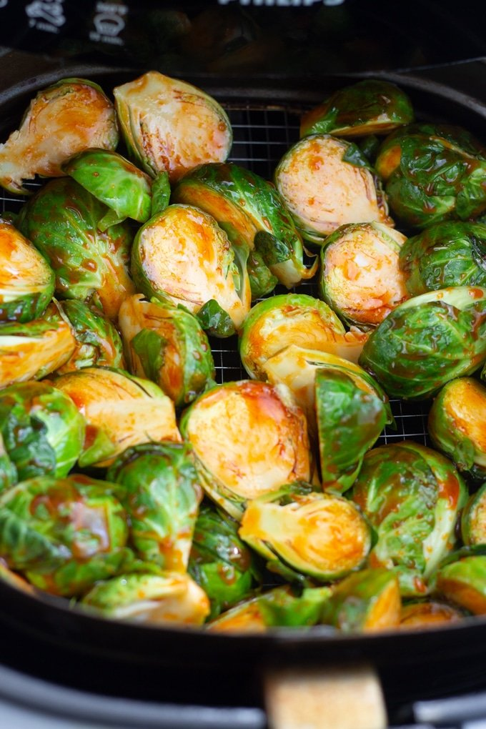 brussels sprouts covered in sauce in air fryer basket