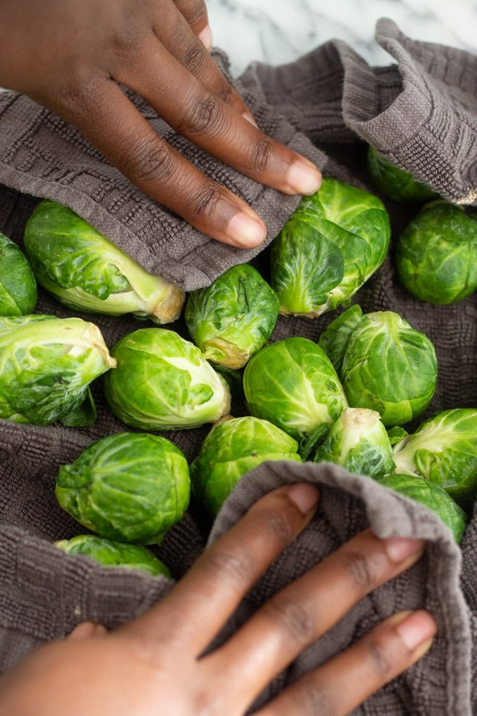 air fryer brussels sprouts in a towel with hands drying them