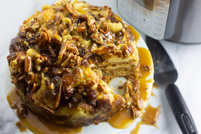 bread pudding on white plate in front of pressure cooker machine