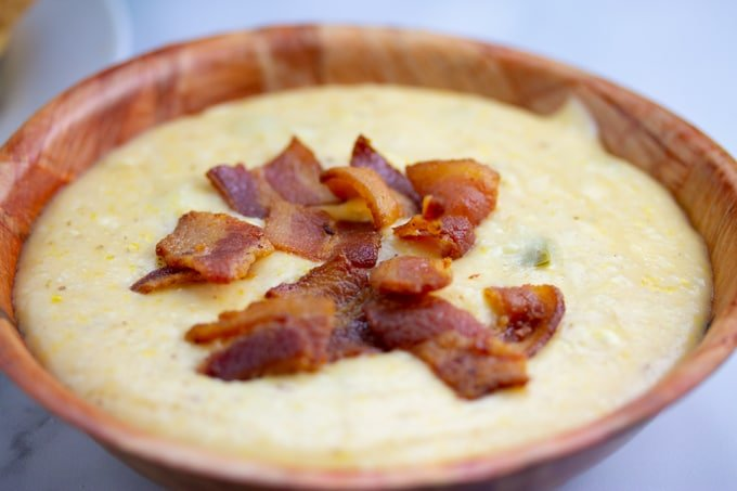 grits in bowl covered with cooked bacon