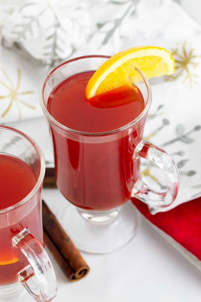 hot holiday punch in a glass with lemon sliced on side
