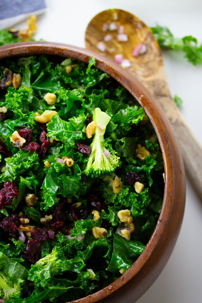 kale and broccoli salad in wooden bowl with wooden spoon to side
