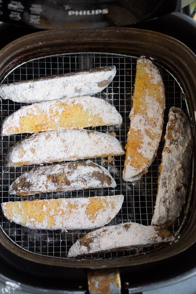 floured potato wedges in air fryer basket
