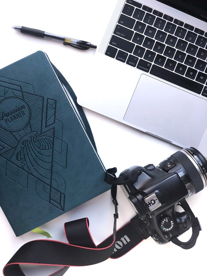 planner, laptop, and dslr camera on white board