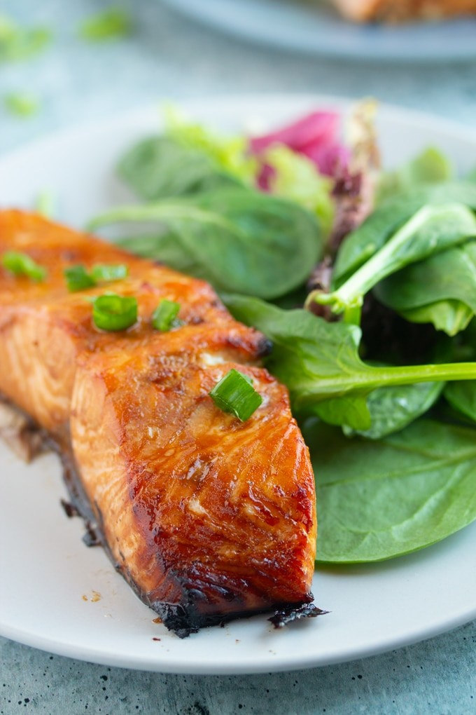 air fryer salmon on a plate next to green salad