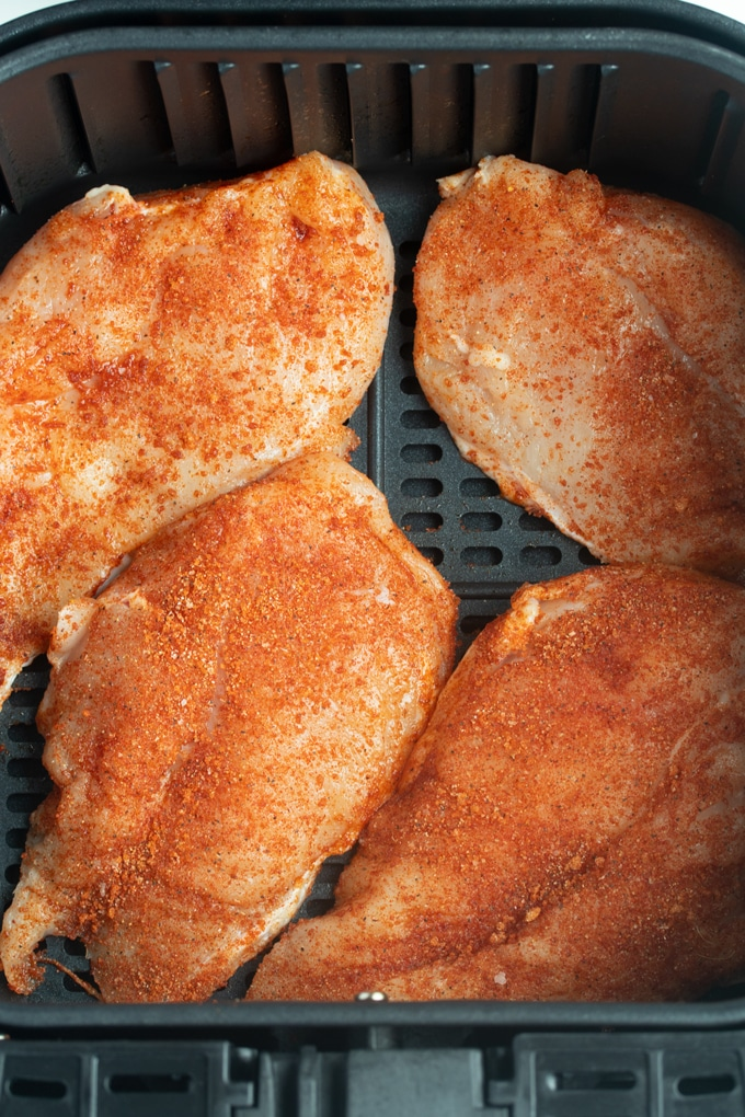 raw chicken breast with seasoning in air fryer basket