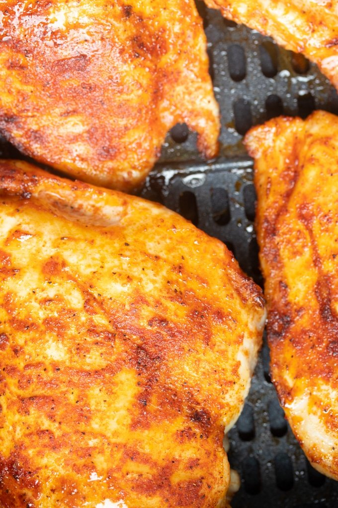 close up of chicken breast in air fryer basket