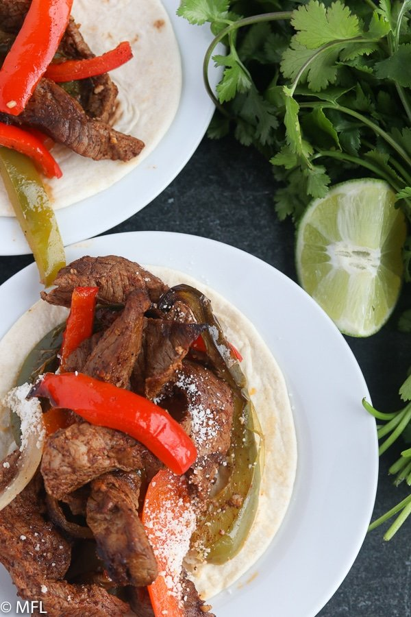 air fryer steak fajita on a plate with cilantro and lime on the side
