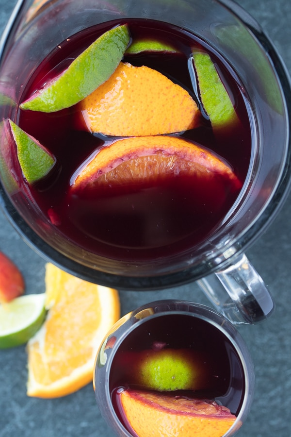 easy red sangria in a pitcher and glass with citrus showing
