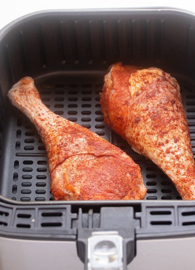 raw seasoned turkey legs in air fryer basket