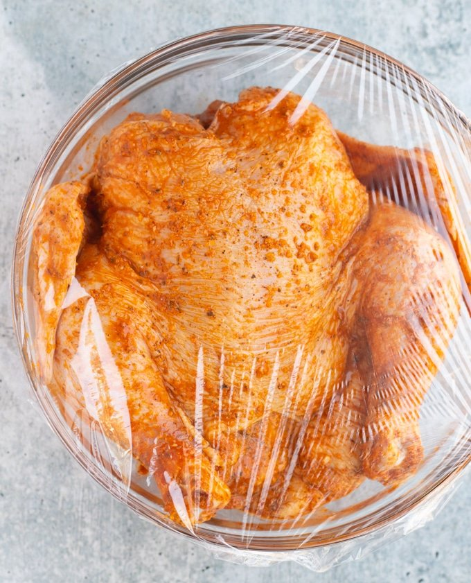 raw whole chicken in bowl in marinade
