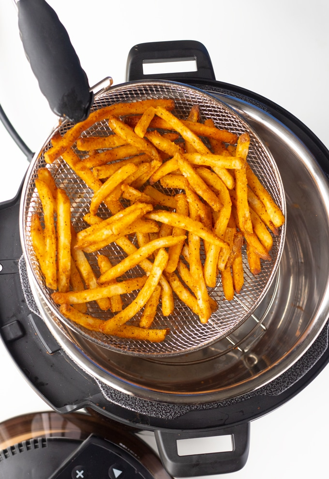 tongs removing fries from mealthy crisp lid basket
