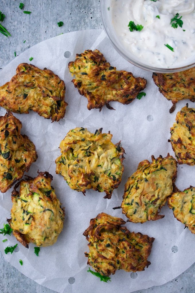 air fryer zucchini fritters laid out on parchment paper with dipping sauce on the side