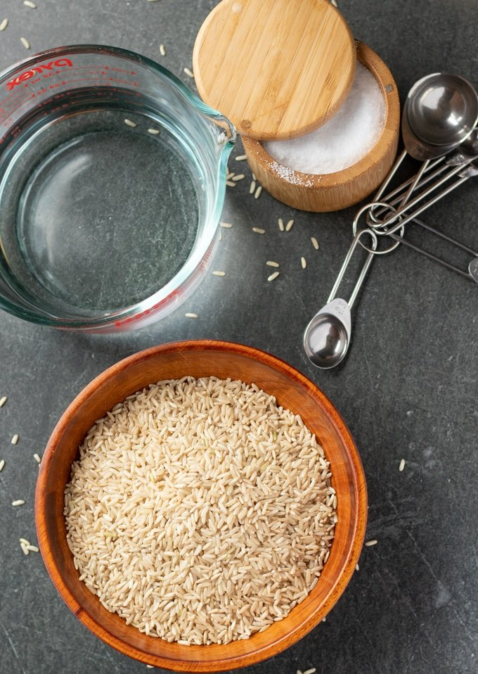 brown rice, salt box, measuring cup with water, and measuring spoons laid out on a gray background