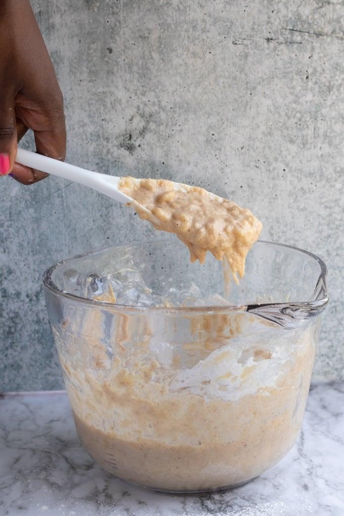 mashed banana fritter batter sliding of spoon into bowl
