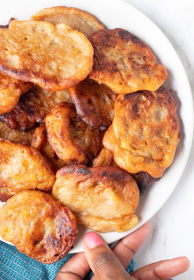 banana fritters on plate with hand touching plate