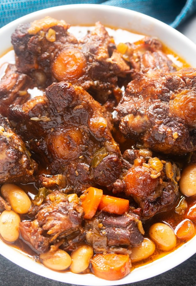 jamaican oxtail in a white bowl with blue napkin in background