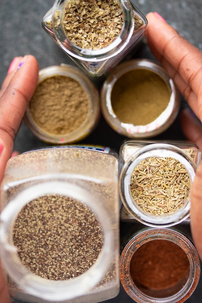 spices in jars with hands surrounding them