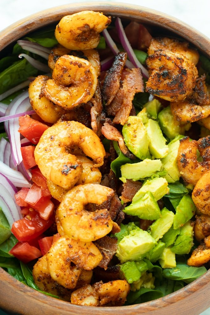 shrimp salad with spinach, shrimp, bacon and avocado in bowl