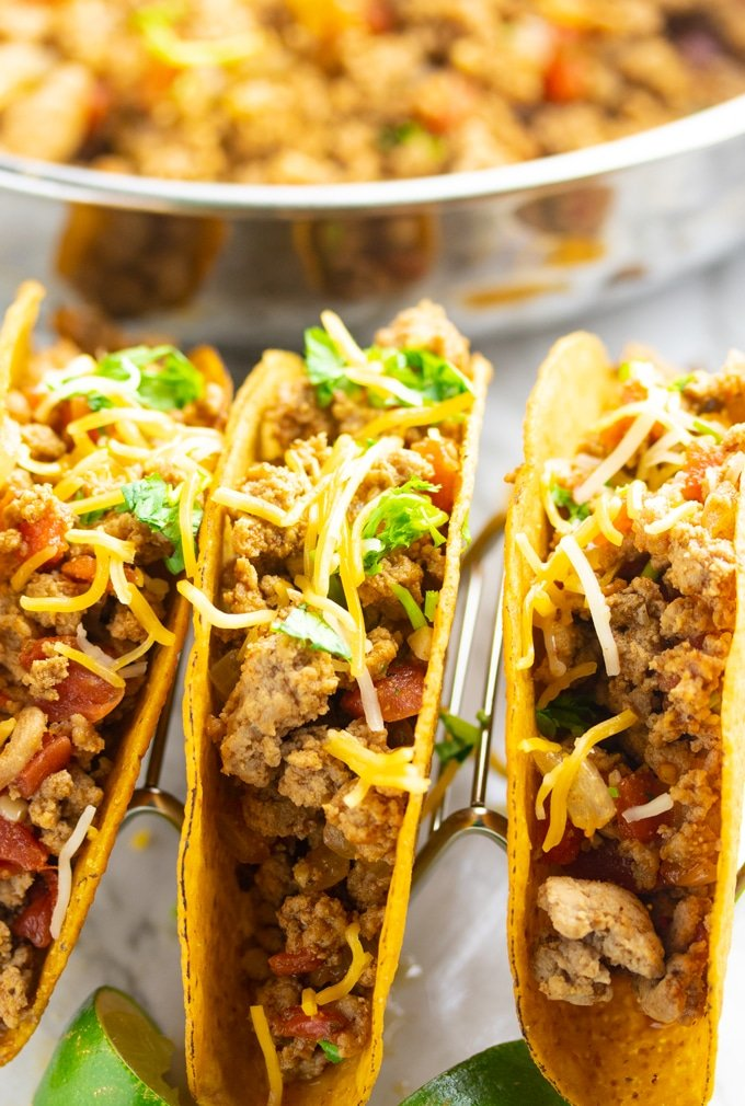 gorund turket taco meat in hard shells topped with cheese and cilantro