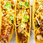 ground turkey tacos in hard shells topped with cheese and cilantro
