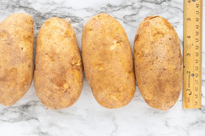 raw potatoes next to a ruler