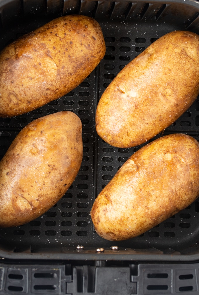 raw potatoes in air fryer basket with salt sprinkled on them