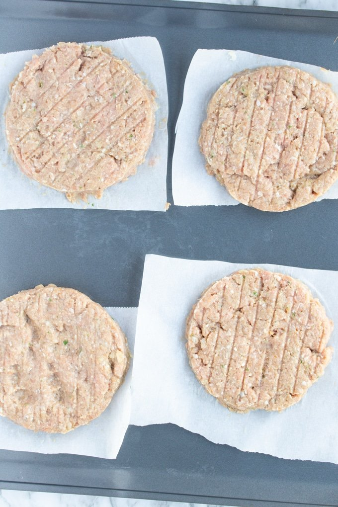 four raw turkey burgers laying on parchment paper