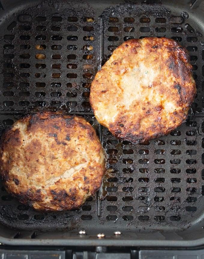 cooked air fryer turkey burgers in air fryer basket