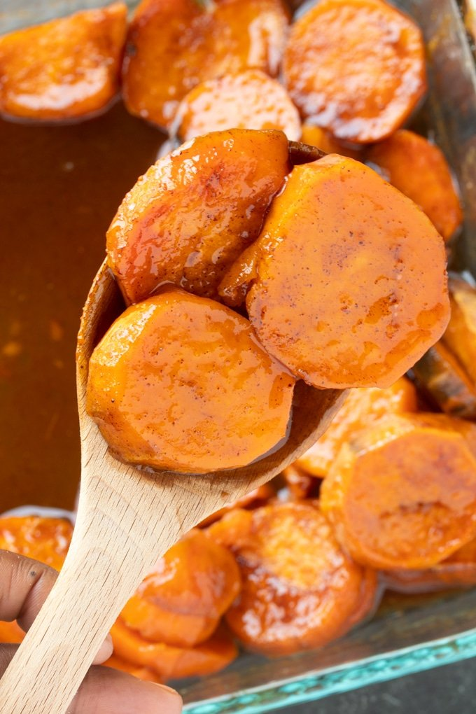 southern candied sweet potatoes sitting on wooden spoon