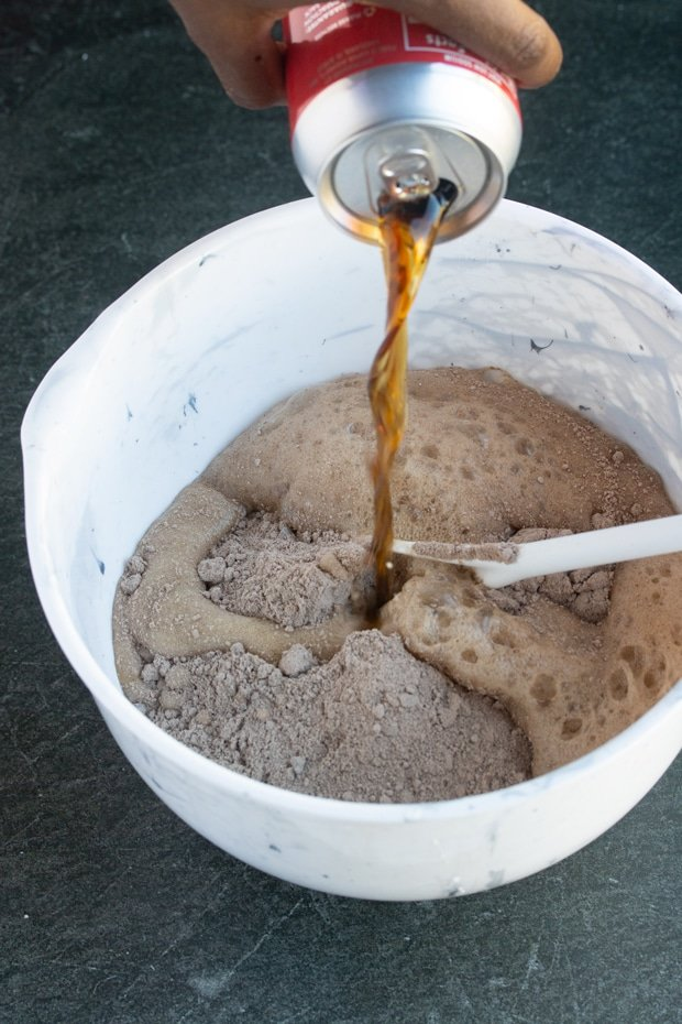 cola soda being poured into bowl with boxed caked mix