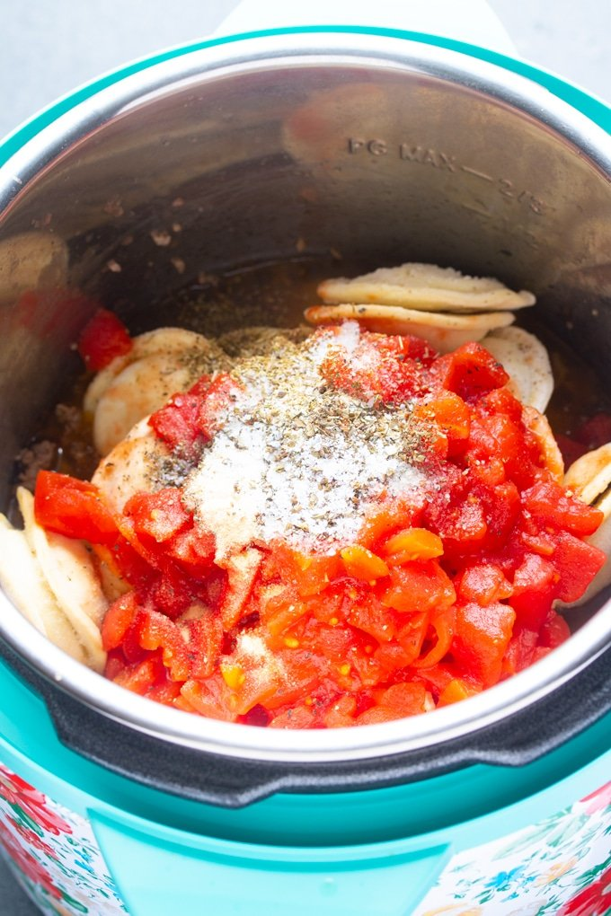 ingredients with ravioli, tomatoes, and seasoning in layers inside the instant pot