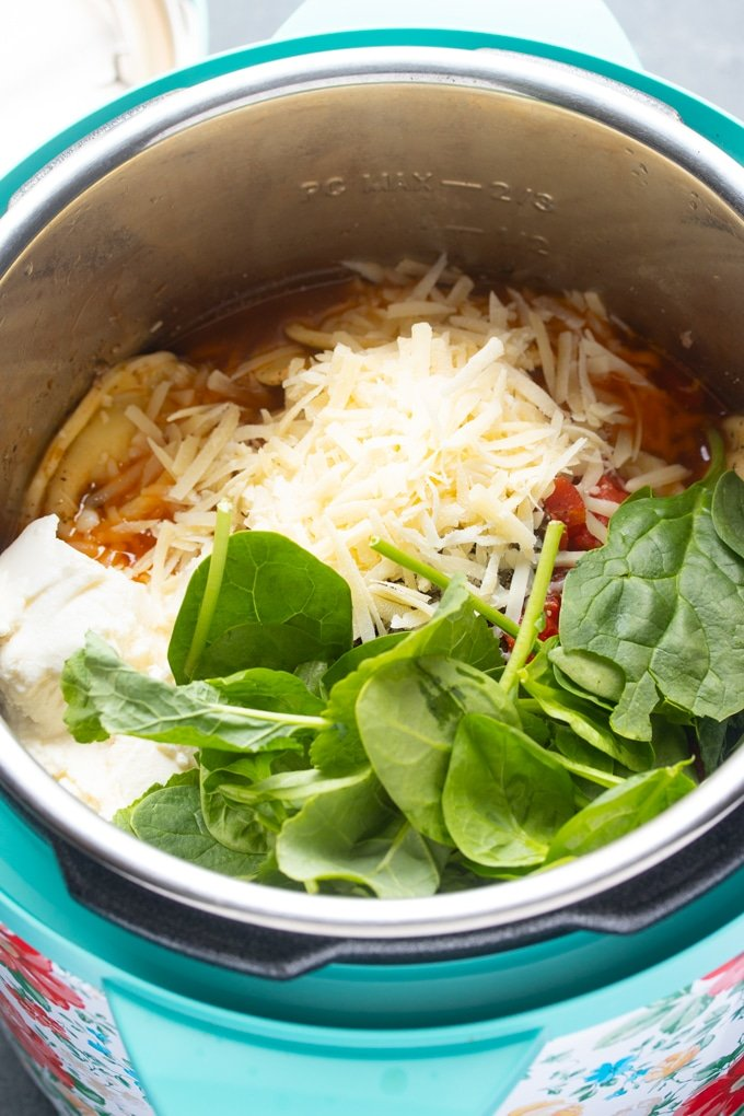 all ingredients inside the instant pot, cheese and spinach on top