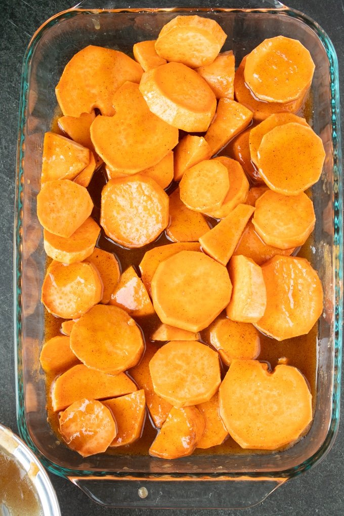 raw sliced sweet potatoes covered in butter sugar mixture