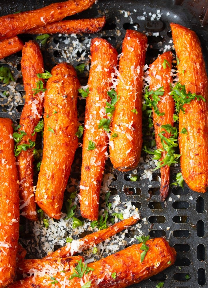 Savory air fryer carrots in air fryer basket topped with parmesan cheese and parsley