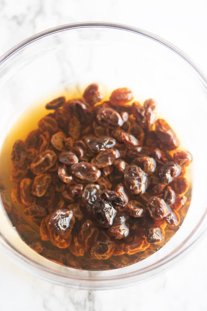 raisins soaking in bourbon in a glass bowl