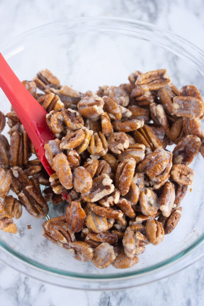 pecans covered in egg whites in bowl with red spatula sticking out